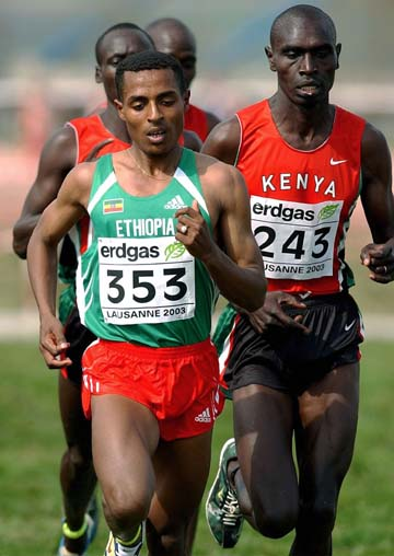 Ethiopian Kenenisa Bekele (L) runs ahead of Kenyan Benjamin Limo (R) during the men's short course race at the IAAF World Cross Country Championships at the Swiss national equestrian center in Avenches, Switzerland, 29 March 2003. Bekele won the race, Limo finished third. AFP PHOTO EPA/KEYSTONE / MARTIAL TREZZINI